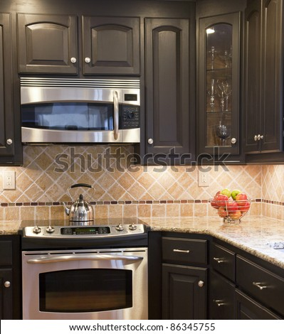 Modern kitchen with dark brown wooden cabinets - stock photo