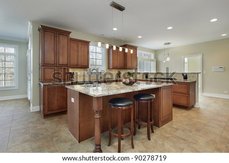 Modern kitchen with granite island and stools - stock photo