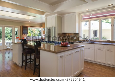 Modern kitchen with island, double refrigerator, cabinets, cherry wooden floor and open ceiling. Kitchen in white with granite counter tops with stainless steel oven and stove. - stock photo