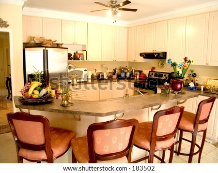 Modern kitchen with island table, four chairs, fridge, stove and ceiling fan.