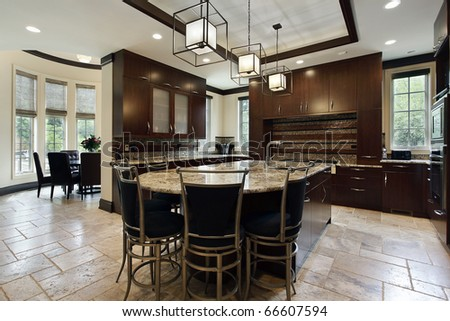 Modern kitchen with large island and circular eating area - stock photo