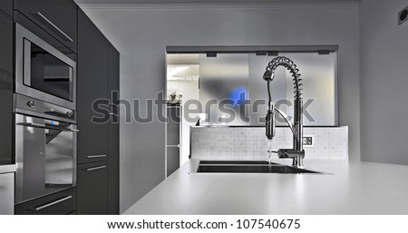 modern kitchen with steel faucet and sliding glass door - stock photo
