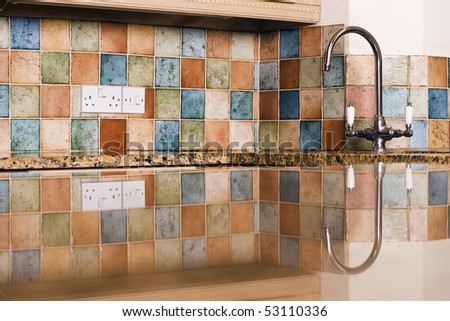 Modern Kitchen With Tiles Reflected In Granite Work Top - stock photo