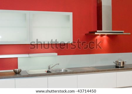Modern kitchen with white furniture and red wall - stock photo