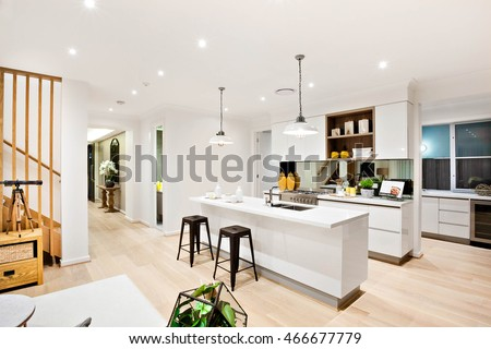 Modern Kitchen With White Walls Illuminated By Hanging Lamps At Night Beside The Wooden Hallway Through