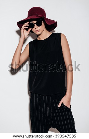 Modern lady. Beautiful young woman in hat adjusting her sunglasses and looking at camera while standing against white background - stock photo