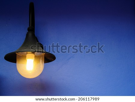 Modern lamp in a blue wall - stock photo