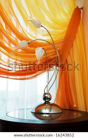 Modern lamp on a background of an orange curtain - stock photo