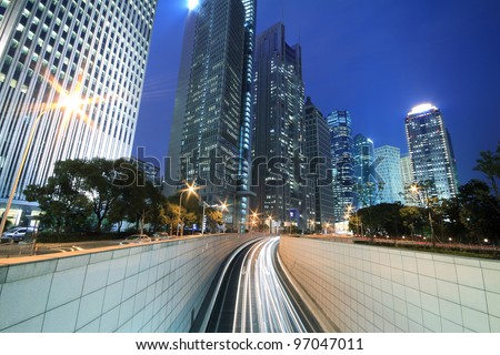 Modern landmark building background of car night with light trails in Shanghai