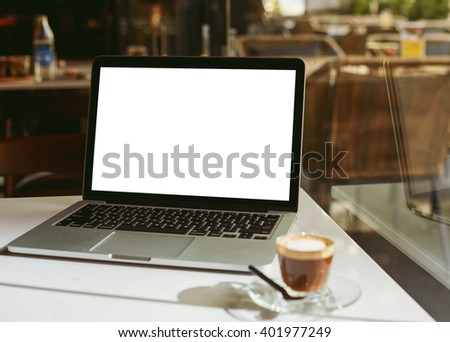 Modern laptop and coffee cup placed on the coffee table in cafe - stock photo