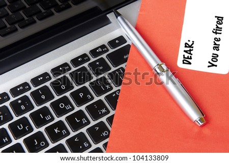 modern laptop and post envelope YOU ARE FIRED with pen - stock photo