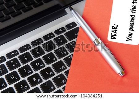 modern laptop and post envelope YOU PASSED with pen - stock photo