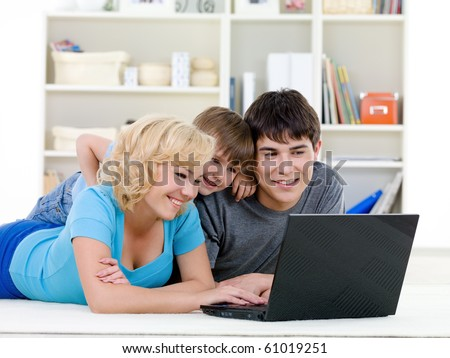 Modern laptop for young happy family with little son - indoors - stock photo