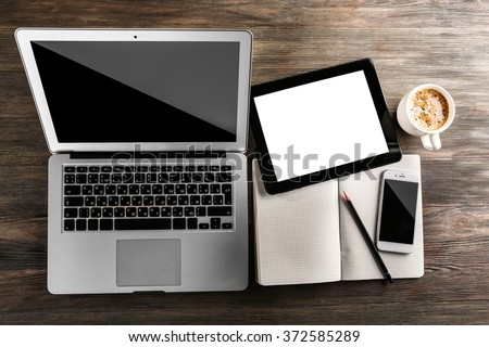 Modern laptop, mobile phone, tablet, notebook and coffee cup on wooden table - stock photo