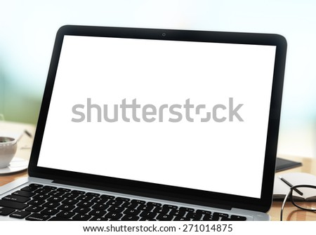 modern laptop on a table with blank white screen - stock photo