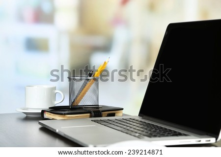 Modern laptop on table, on light background - stock photo