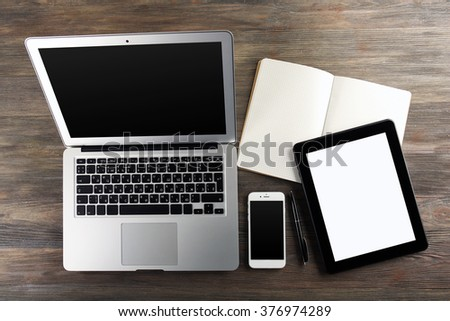 Modern laptop, tablet, mobile phone and notebook on the table - stock photo