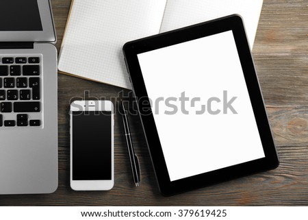 Modern laptop, tablet, mobile phone and notebook on the table, close-up - stock photo