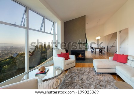 Modern large living room with breathtaking view, high ceiling, white couch, hardwood floor, fire place, rug and round glass table. - stock photo