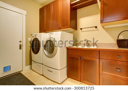 Modern laundry room with tile floor, also washer and dryer. - stock photo