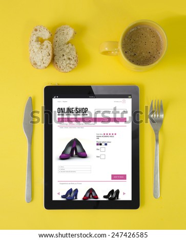 modern lifestyle or technology addiction concept: tablet with online shop on the screen and breakfast - stock photo