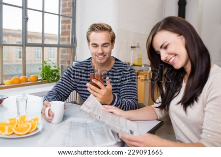 Modern lifestyle with a young couple sitting at the breakfast table reading the newspaper and checking messages on their mobile phone - stock photo