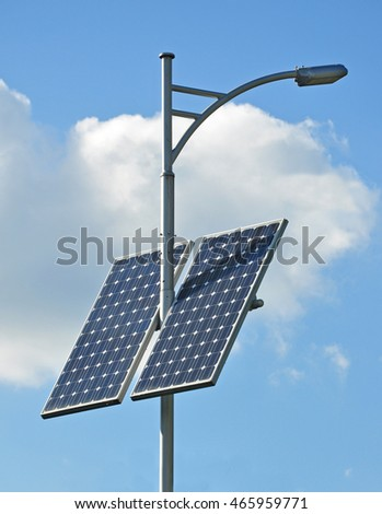 Modern light support with a lantern and installed solar panels on a blue sky background.