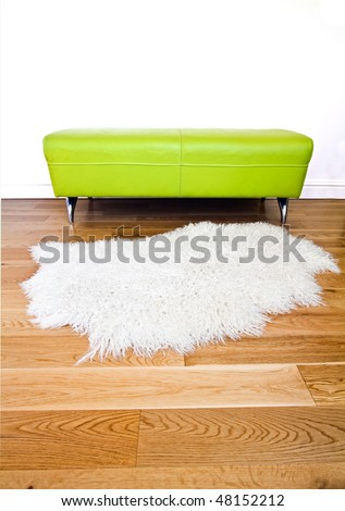 Modern lime green furniture set against a white wall on  polished wooden floor also featuring an angora fleece