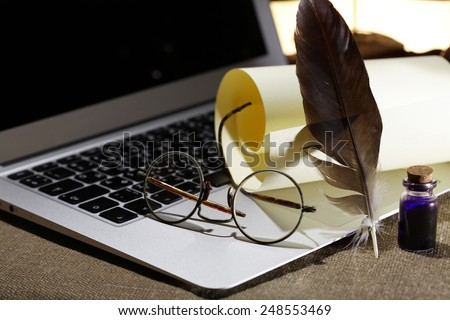Modern literature. Still life with scroll and quill on modern laptop - stock photo