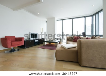 Modern living area with floor to ceiling windows - stock photo