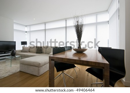 Modern living area with large designer sofa and wooden dining table for four - stock photo
