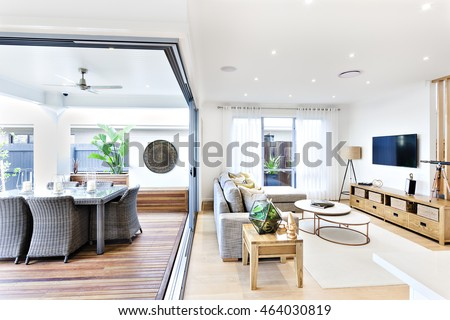 Modern living room attached to the patio and dining area including a plastic chairs and tables on the wooden floor outside near to the sofa and pillows on the carpet beside the television and cabinet