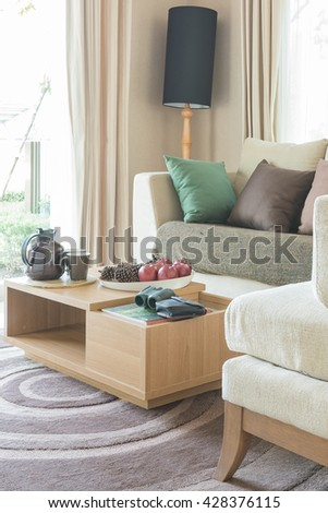 modern living room design with wooden table on carpet and black lamp