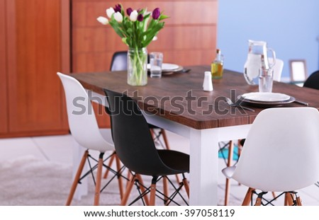 Modern living room. Furniture set with table and chairs. Bouquet of beautiful white and purple tulips on the table - stock photo