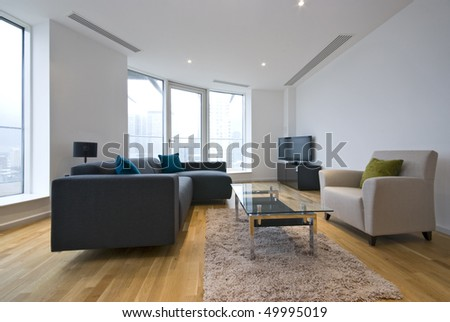 Modern living room in a penthouse apartment with large contemporary sofa - stock photo