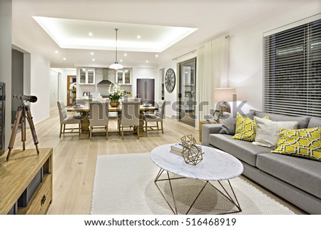 Modern Living Room Including Sofas Chairs And Tables Beside The Kitchen Dining Illuminated