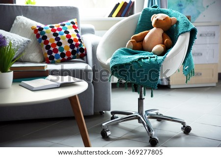 Modern living room interior in grey tones with bright blue plaid and teddy bear on chair - stock photo