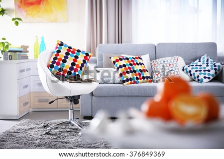 Modern living room interior in grey tones with colourful pillow on chair