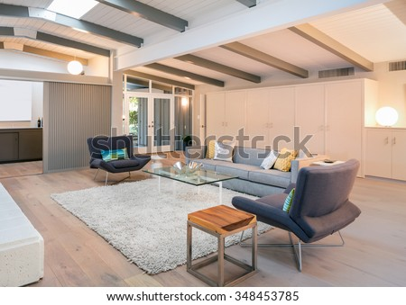 Modern living room interior in mid century home with couch, hand-woven natural fine sisal rug, glass table, designer chairs in open space. - stock photo