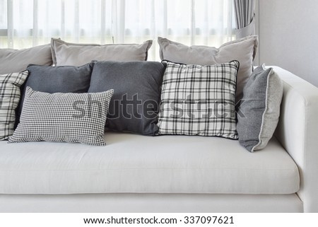 modern living room interior with black and white checked pattern pillows on sofa - stock photo