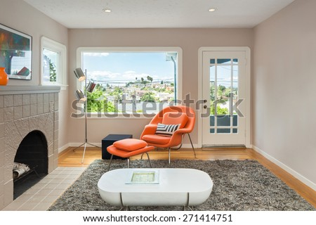 Modern living room interior with fire place, view window, orange designer relaxing chair and white designer table with natural colored fine sisal rug in open space living room. - stock photo