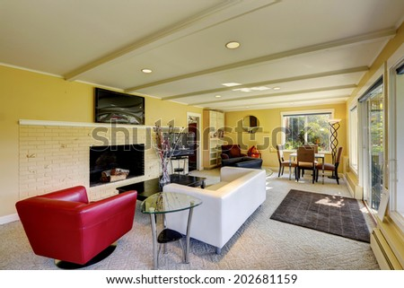Modern living room interior with tv, fireplace, red and white sofas. VIew of small dining area