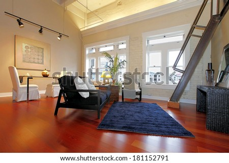 Modern living room with brick painted wall, high ceiling, hardwood floor and iron steep stairs. Furnished with classic elegant furniture - stock photo