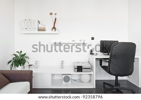 Modern living room with computer desk and the screen, sofa and table with white carpet on dark brown wooden floor - stock photo