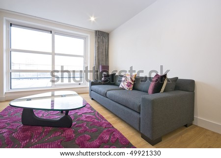 Modern living room with designer furniture and big floor to ceiling window - stock photo