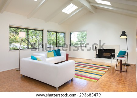 Modern living room with fire place, colorful rug, chair and ceiling / view windows.  - stock photo