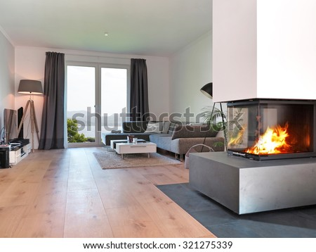 modern living room with fireplace and a view to the coast - stock photo