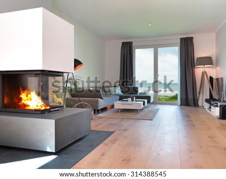 modern living room with fireplace and a view to the sea - stock photo