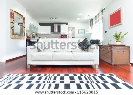 Modern living room with sofa and checkered carpet - stock photo