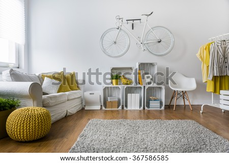 Modern living room with sofa, carpet, wood panels and bike hanging on wall - stock photo